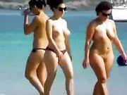 Zwei Frauen, die oben ohne und Nackt am Strand